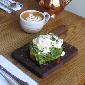 Farm to table tartine and cappuccino in Brooklyn cafe with outdoor seating